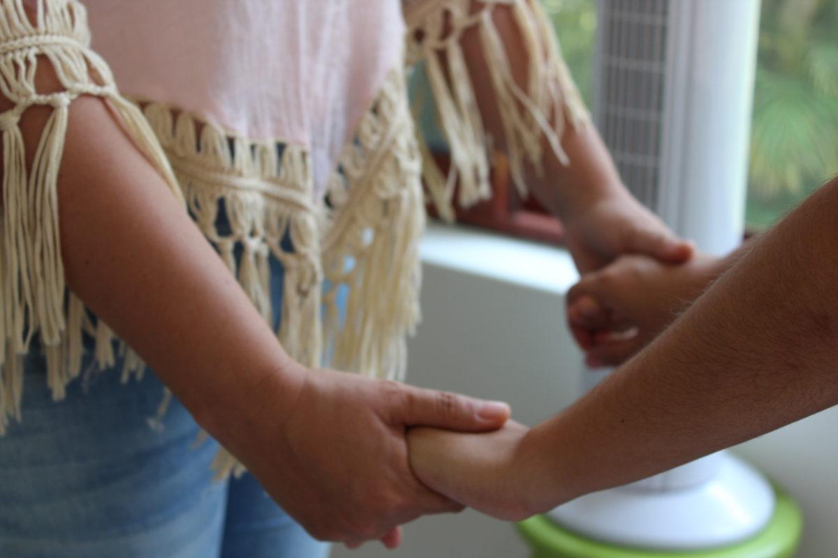 Dos mujeres frente a frente con las dos manos entrelazadas
