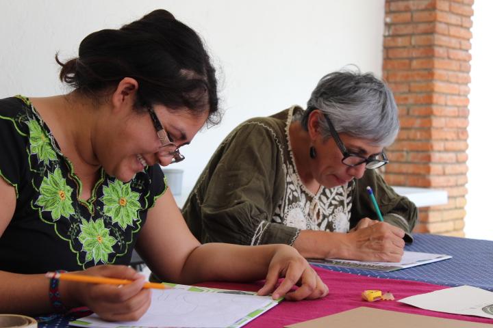 Dos mujeres escribiendo sobre una hoja de papel concentradas y sonrientes