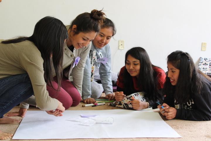 Cinco jovenes sentadas sobre el piso dibujando sobre una hoja de rotafolio
