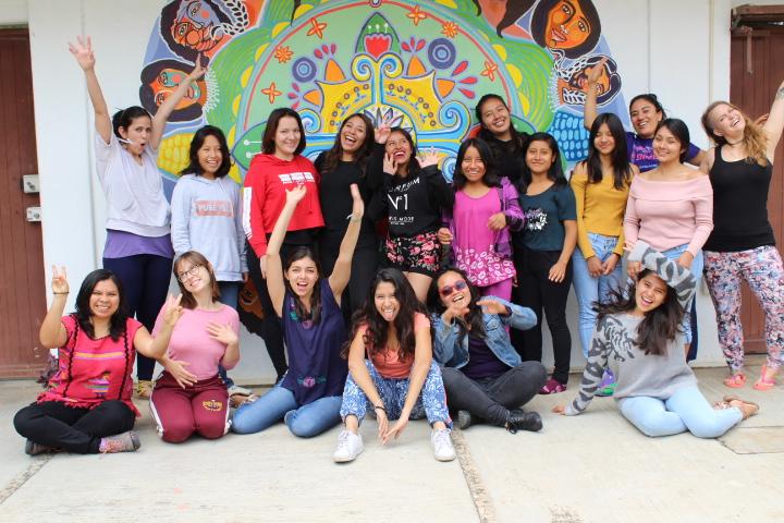 Un grupo de 17 mujeres en media luna posan para la foto, de fondo un mandala de mujeres y maíces