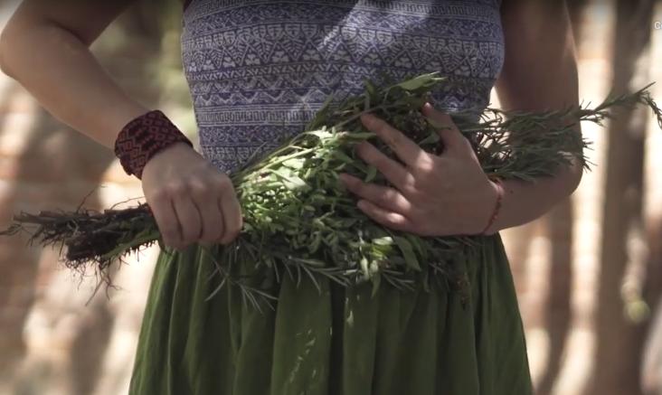 Una mujer sostiene con su mano derecha un ramo con ruda, romero y albahaca que esta en su ombligo