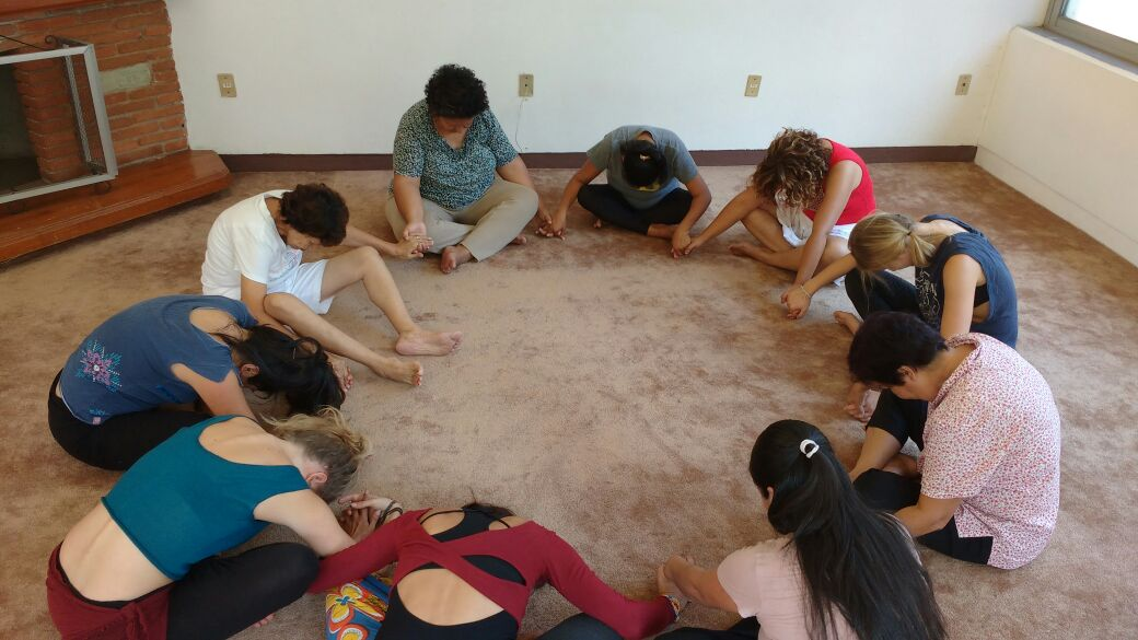 Un circulo de mujeres sentadas con las piernas cruzadas y tomadas de las manos haciendo una reverencia de agradecimiento